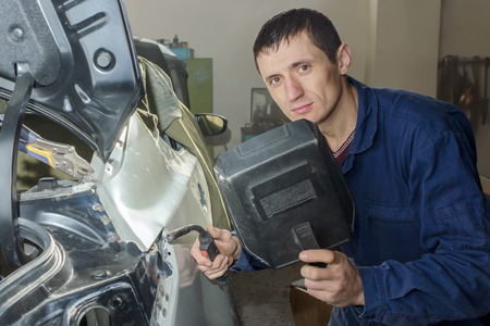 Young mechanic with welding unit in the workshop