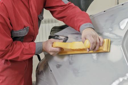 garage automobile: peintre de voitures prépare l'aile arrière de la voiture pour la peinture.