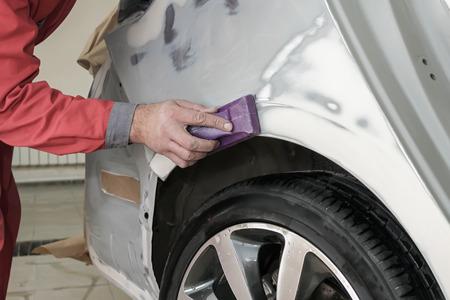 body paint: pintor de carros prepara el alerón trasero del coche para la pintura.
