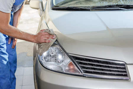 The worker polishes optics of headlights of the car to restore gloss and transparency