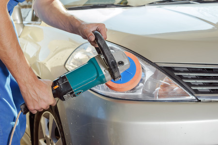 The worker polishes optics of headlights of the car with the electric tool. Standard-Bild