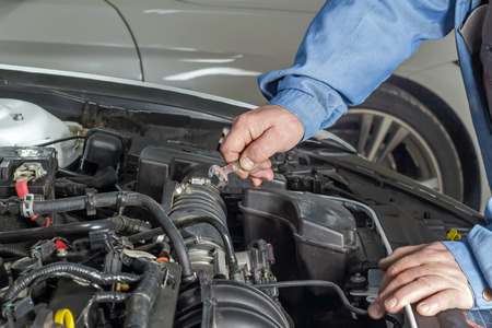 Hand atomomechanics holding the key for repairing the engine of the car.