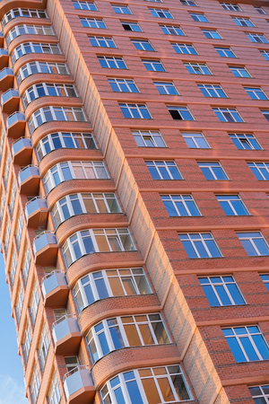Beautiful facade of a new multi-storey residential building made of red brick.
