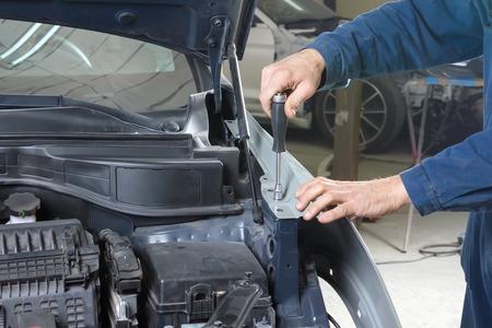 Mecánico de automóviles repara la carrocería de un vehículo después de un accidente de tráfico