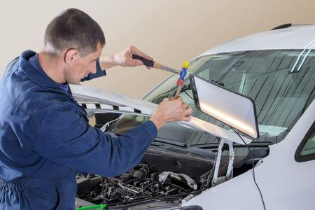 Professional mechanic removes dents on the car body Standard-Bild