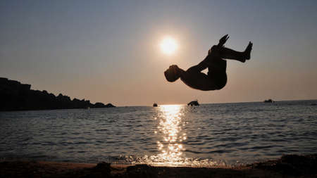 backflip: A boy jumping backflip in front of the sea during sunset