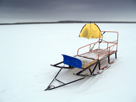 Tent and sledges on a winter lake under terrible clouds