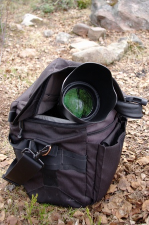 Camerabag with photo lense outdoor on dry leaves Stock Photo