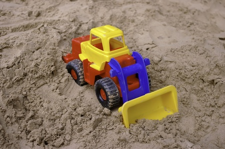 The bright-colored toy tractor on the sand