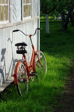 Red old bicycle on the grass near old wooden house wall Stock Photo