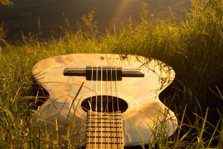 Black guitar in grass at sunset