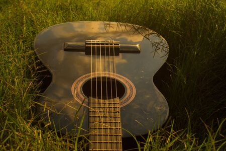 Black guitar in grass at sunset Stock Photo