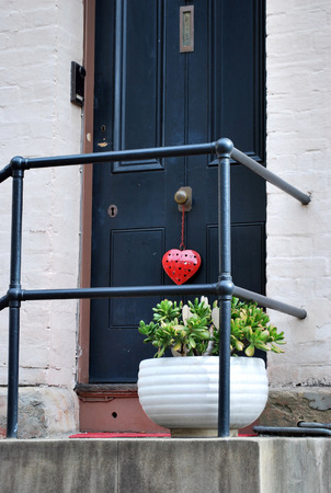 Cosy home entrance porch with a plant and a heart on a door knob