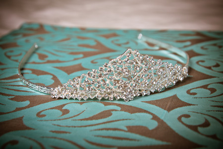 Silver sparkly bridal or prom tiara on turquoise with brown background Stock Photo
