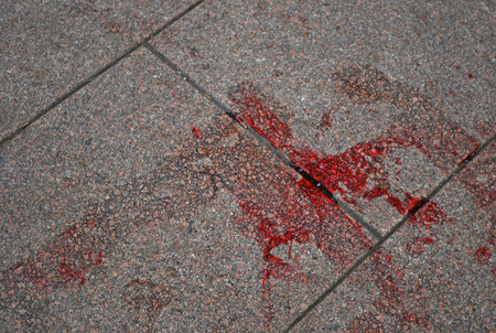 Blood left on a tile at the place of crime scene. Stain on old granite texture Stock Photo