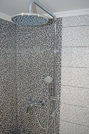 Chrome massage shower head and rail on grey square tiles background Banco de Imagens