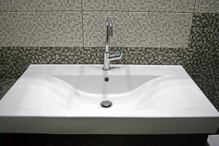 curve: Detail of a rectangular white sink on grey mosaic tiles background Stock Photo