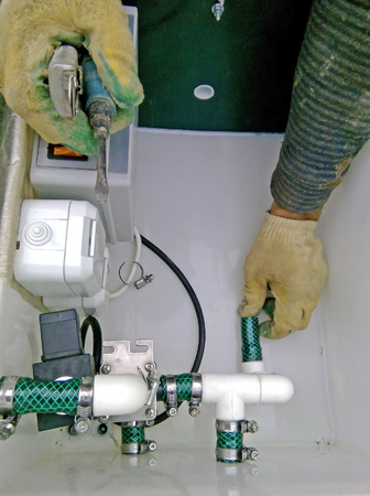 Plumbing building contractor repairing plastic pipe in waste treatment tank (septic system) Editorial