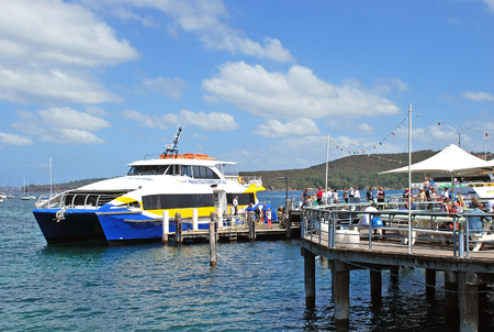 Sydney, Australia - October 11, 2015: Manly Fast Ferry boat at Manly wharf ready to pick up passengers and depart to Sydney Cirqular Quay in the summer noon.
