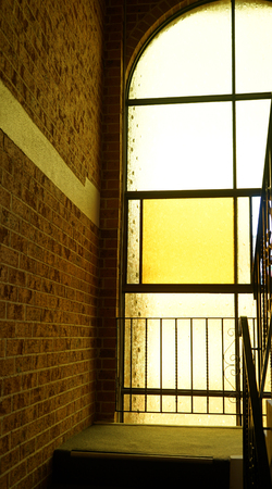 Vintage tall gothic glass window (stained glass yellow light version) on a staircase in residential building Banco de Imagens