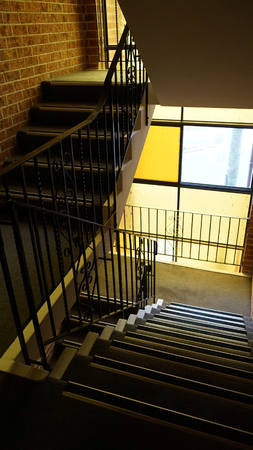 Two carpeted passageways as part of the stairs in a modern residential building. Interior including brick wall and yellow stained glass window.