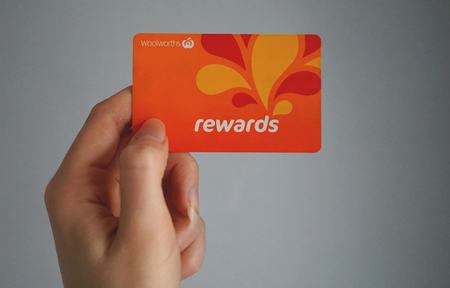 Sydney, Australia - October 15, 2017: Female caucasian hand is holding a Woolworths Rewards loyalty card, this loyalty program gives money off shopping. Woolworths Supermarkets is an Australian market leader grocery store chain.