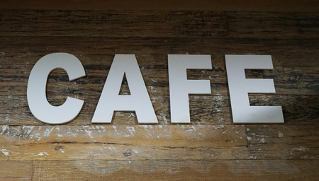 White letters spelling the word CAFE laid out on aged wooden parquet background