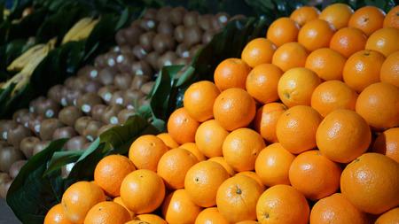 Fresh organic fruits (oranges, kiwi, bananas) on display in supermarket, farmers market Banco de Imagens