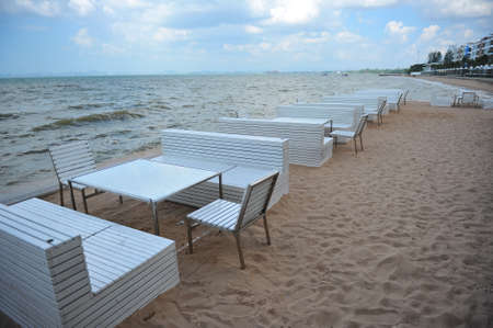 Table chair set beside sea scenic background
