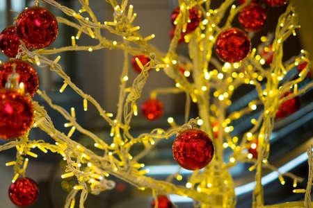 Red christmas balls hanging on the lighting tree Stock Photo