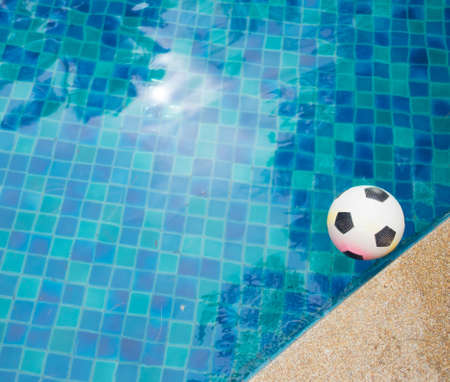 A plastic football floating in the blue water of a swimming pool