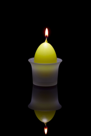 paschal: Paschal candle in the form of eggs in a glass candlestick on a black background. Stock Photo