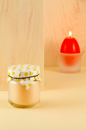 easter candle is burning: Easter treat - peachy jam and a burning candle in the shape of an egg on a light background of wood an alder