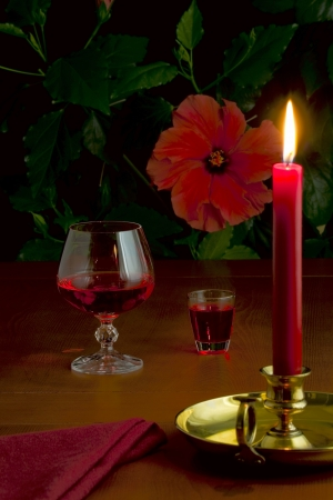 On the table a glass with red wine, a small glass with liquor and a burning candle in a candlestick