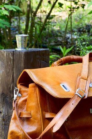 collapsible: Carpetbag next to a wooden column and collapsible cup Stock Photo