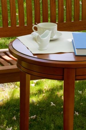 Sobre la mesa en el jardín de una taza de té y jarra de leche Foto de archivo - 20218133