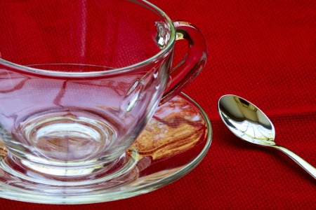 textural: Beautiful tea service - a saucer, a spoon and a cup on a red background textural Stock Photo