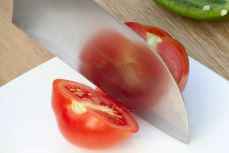 Knife� cuts the ripe tomato on a white plate photo