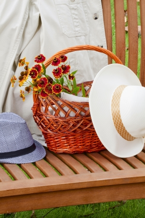 A bench on the grass on the bench white jacket men's and women's hats basket and bunch of flowers photo