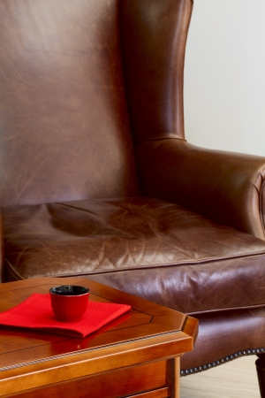 Coffee table a cup for coffee on a napkin and a leather armchair photo