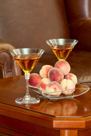 On the coffee table peaches in a vase and two glasses of wine on the background of the leather armchair photo