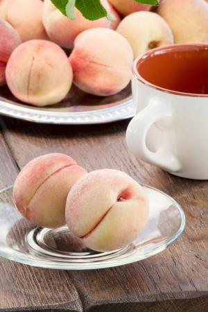 goldish: Goldish velvety ripe peaches on a glass saucer