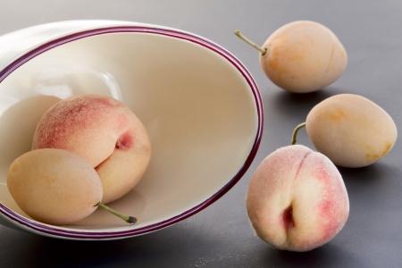velvety: Ripe goldish velvety peaches and yellow plums Stock Photo