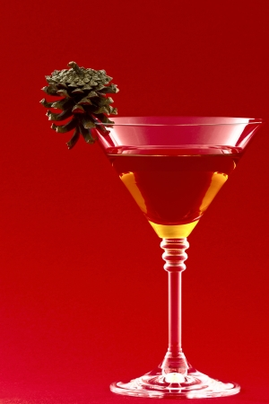 Glass with a cocktail and a pine cone on a red background photo