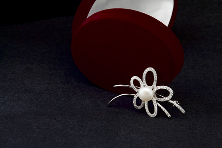 Silver brooch with pearls on a black background Stock Photo