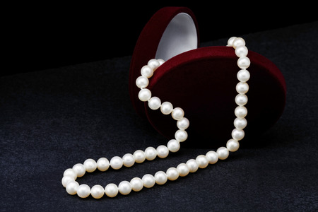 Pearl necklace next to a box for jewelry on a black background photo