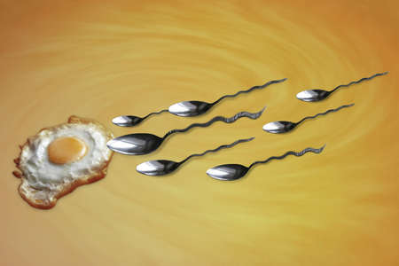 Concept of reproduction, with sperm swimming toward the egg Archivio Fotografico