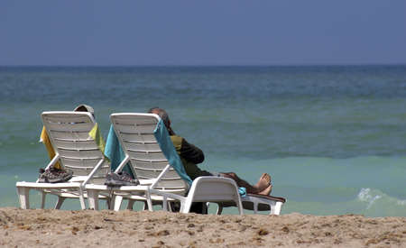 Rear view of a couple relaxing on lounge chair looking at the ocean on a beautiful beach