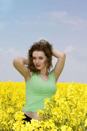 Portrait of a seductive young woman in rape flower field photo