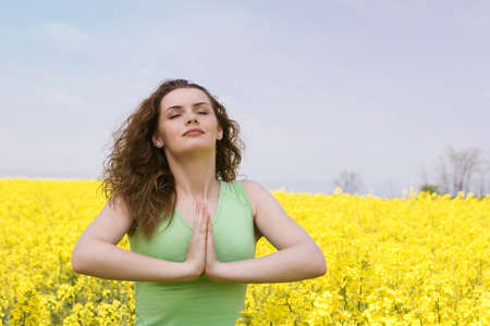 Portrait of a young woman praying in rape flower field